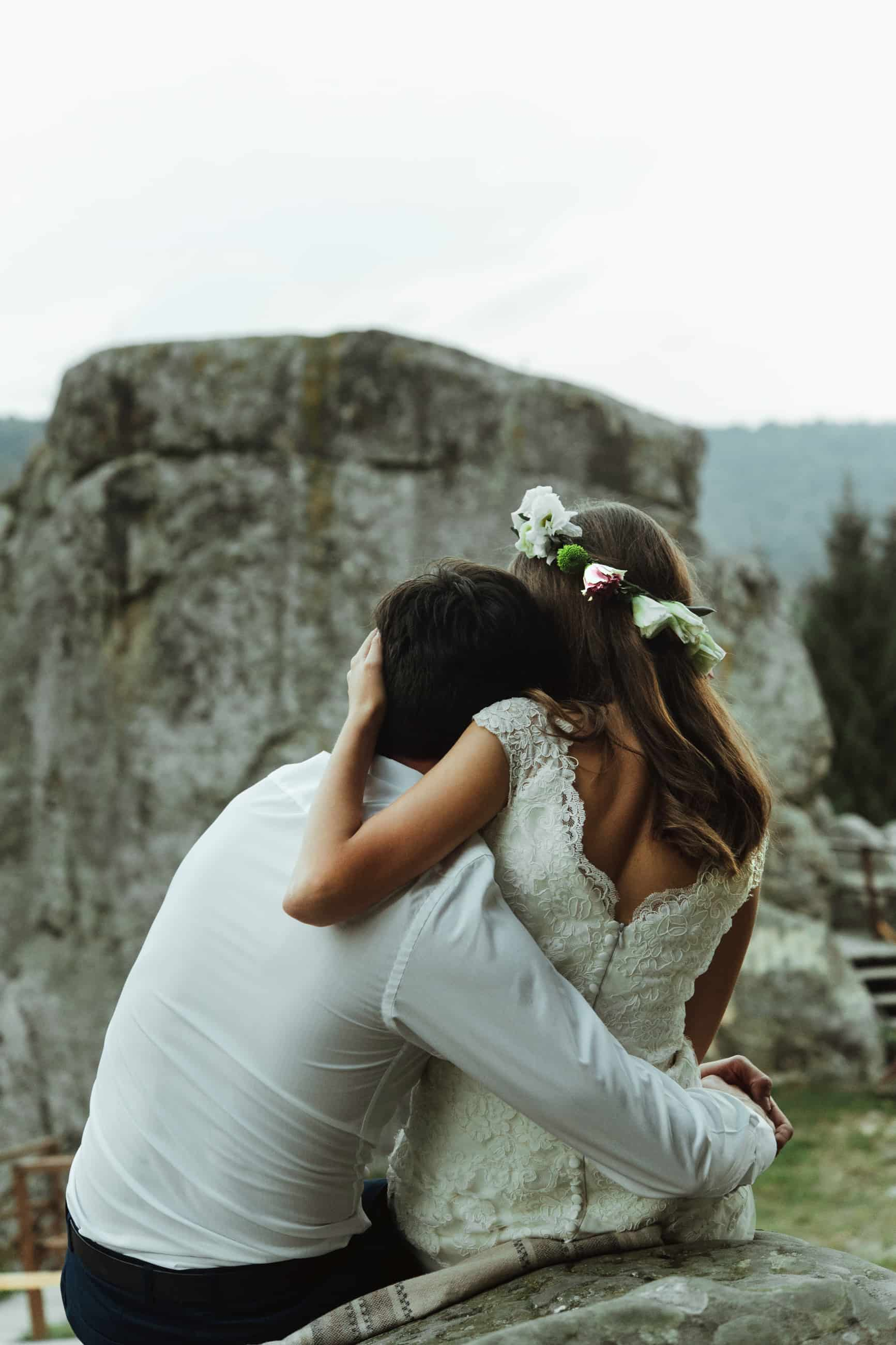 happy luxury couple of newlyweds hugging with tender on the top of a mountains in the evening
